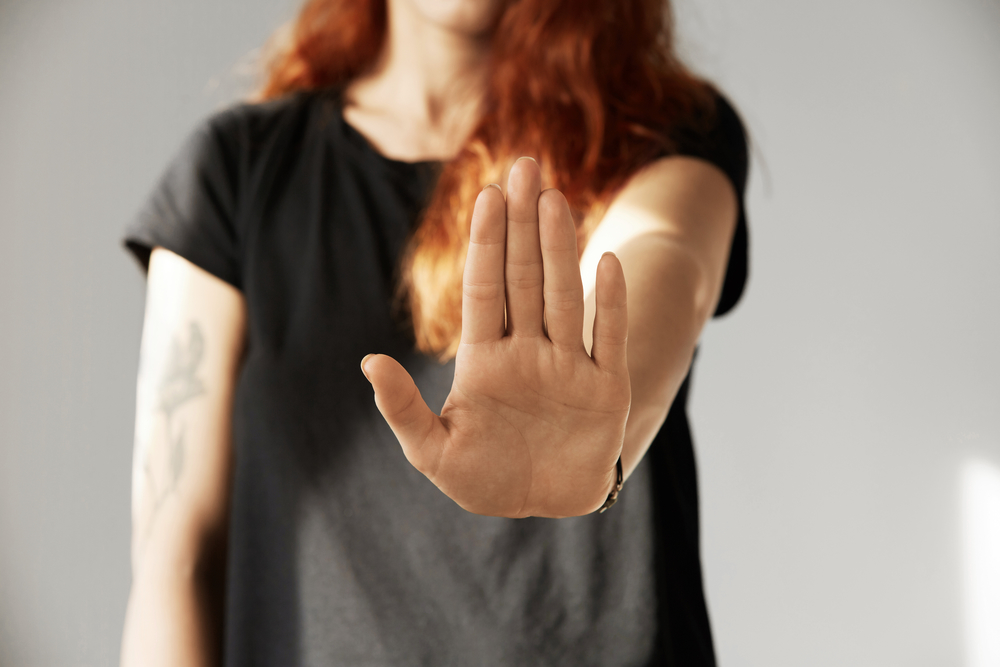 Cropped isolated view of young woman with red hair making stop gesture with her palm. Portrait of teenager girl wearing black T-shirt showing stop sign while arguing with her parents. Body language